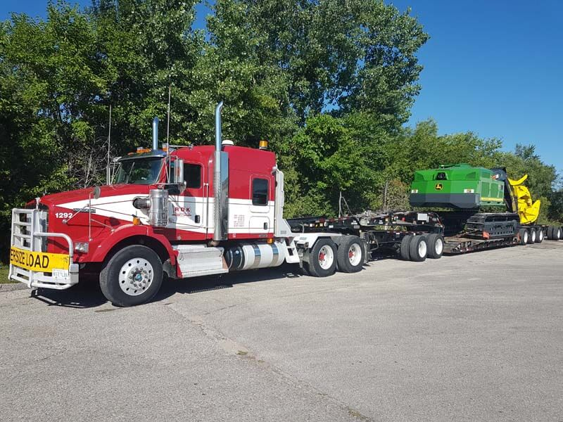 Truck hauling farm equipment